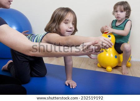 a female physiotherapist makes physiotherapy with young children