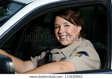 a female police officer smiles while sitting in her patrol car.