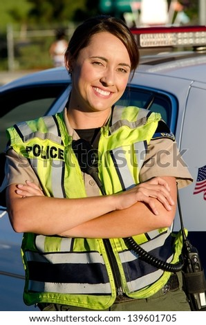 a female police officer smiling as she crosses her arms in front of her partrol car.