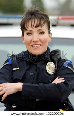 a female police officer smiling next to her police car. - stock photo