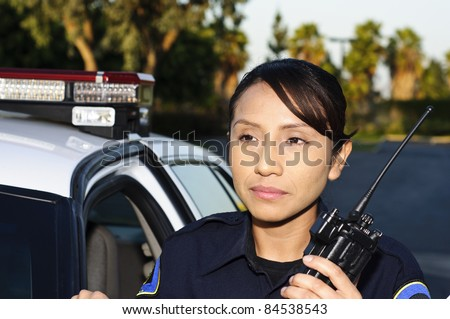 a female police officer standing next to her unit while she's about to talk on her radio. - stock photo