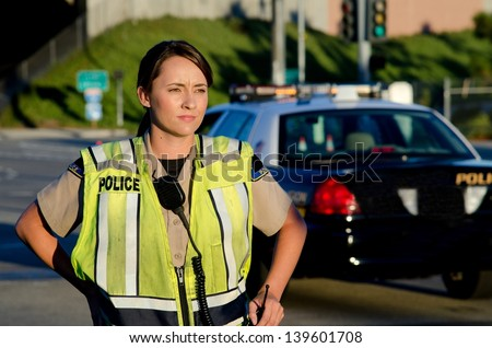 A female police officer staring and looking serious during a traffic control shift.