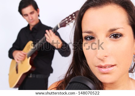 A female singer and a male guitarist in action in white background - stock photo