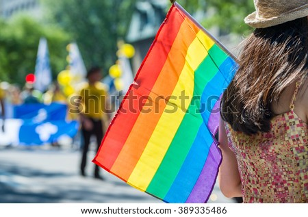 A female spectator is holding the gay rainbow flag at the 2015 Gay Pride Parade in Montreal. - stock photo
