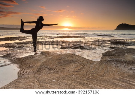 A female standing and balancing on one leg practicing a yoga pose, King Dancer Natarajasana;, one of the many asanas to master in yoga.  Behind her the beautiful sunrise