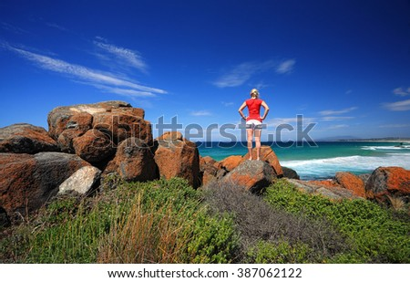 A female standing on the vibrant orange rocks and looking out to sea.  Bingie Point, Eurobodalla National Park on the Sapphire Coast of NSW, Australia.  Mount Gulaga in the far distance
