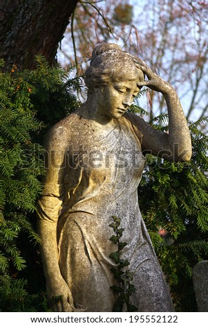 a female statue in front of a hedge