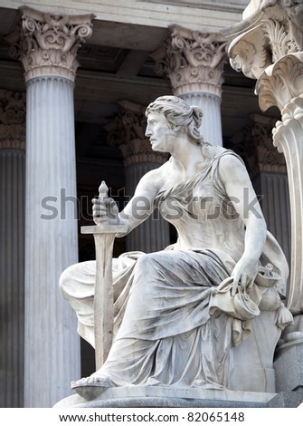 A female statue representing the executive powers of the state, part of the The Athena Fountain (Pallas-Athene-Brunnen) situated in front of the building of Austrian Parliament. - stock photo