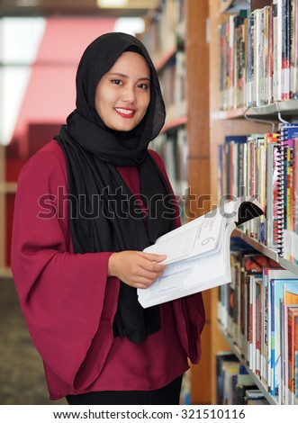 A female student in a library. - stock photo