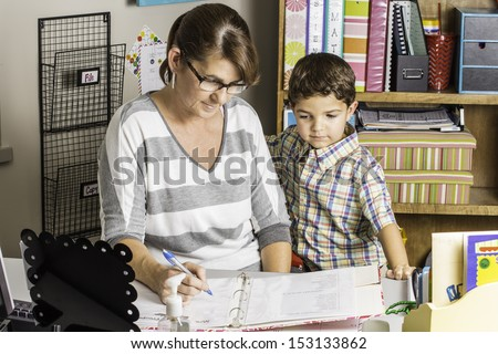 A female teacher helping a young student at her desk.