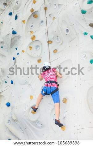 A female teenager climbing a rock wall halfway to the top - stock photo