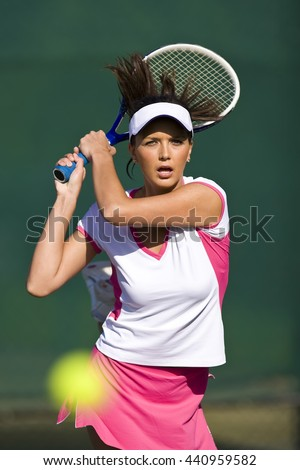 A Female Tennis Player Volleys ball - stock photo