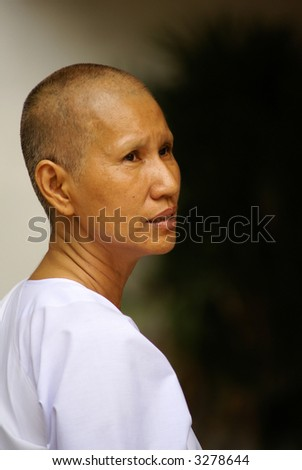 A female Thai monk dressed in white. - stock photo