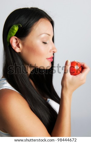A female with a tomato and a chilli pepper - stock photo
