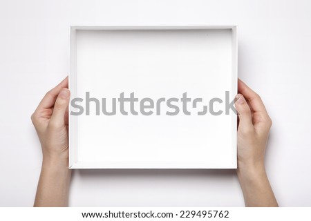 A female(woman, girl) two hands hold the empty(blank) white box isolated white, top view at the studio. - stock photo