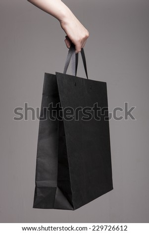A female(woman) hand hold a black shopping bag(paper bag) and black strings at the studio. - stock photo
