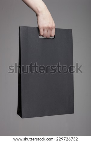A female(woman) hand hold a black shopping bag(paper bag) at the studio. - stock photo