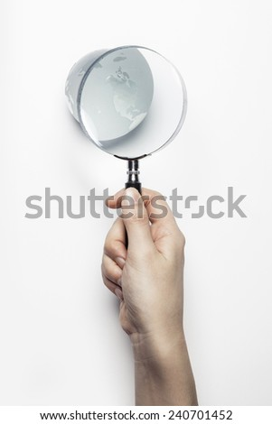 A female(woman) hand hold a magnifier(reading glass) into the glass globe isolated white at the studio. - stock photo