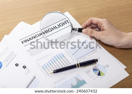 A female(woman) hand hold a magnifier(reading glass) point to graph paper(document), pen on the office desk(table). - stock photo