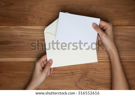 A female(woman) hand hold(open) a envelope and post card on the wood desk, top view at the studio. - stock photo