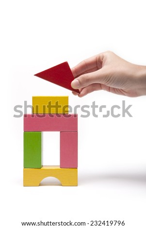 A female(woman) hand hold(pick up) a house(building, tower) made with color wood blocks isolated white at the studio.