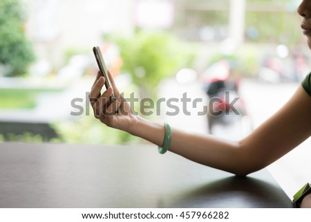 A female(woman) hand hold(touch) and looking at smart phone.