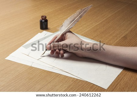 A female(woman) hand hold(write) a feather quill pen with ink on the letter paper and wood desk(table) at the studio. - stock photo