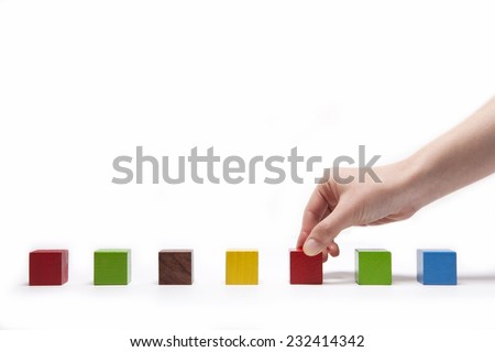 A female(woman) hand pick up(hold) a wood block among many color(red, green, blue, yellow) wood blocks isolated white at the studio. - stock photo