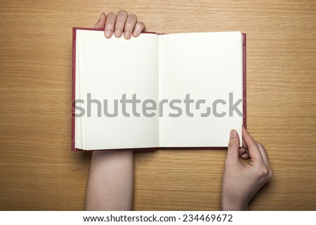 A female(woman) hands hold a blank(empty) book(note, diary) on the wood desk(table), top view at the studio. - stock photo