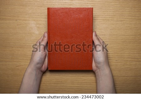 A female(woman) hands hold a blank(empty) red book(note, diary) on the wood desk(table), top view at the studio. - stock photo