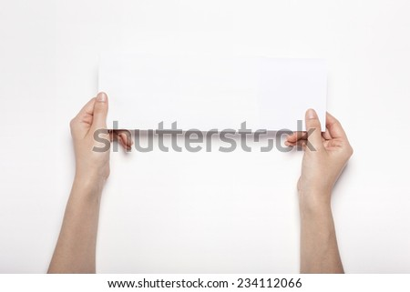 A female(woman) hands hold a empty(blank) white envelope isolated white, top view at the studio. - stock photo