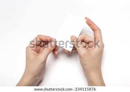 A female(woman) hands hold a empty(blank) white name card isolated white, top view at the studio.