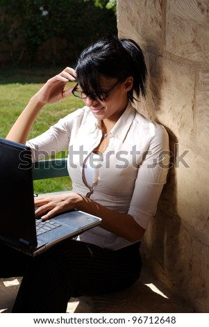 A female working on a lap top in a garden space - stock photo