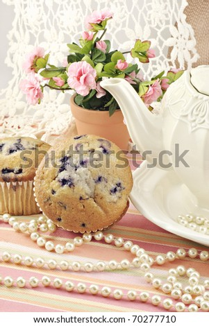 A feminine tea party with fresh baked blueberry muffins, antique pearls and lace, and teapot - stock photo