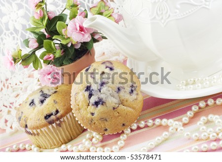 A feminine tea party with fresh blueberry muffins, roses, lace and pearls - stock photo