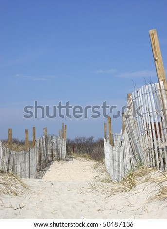 A fenced- in path leading to the beach - stock photo