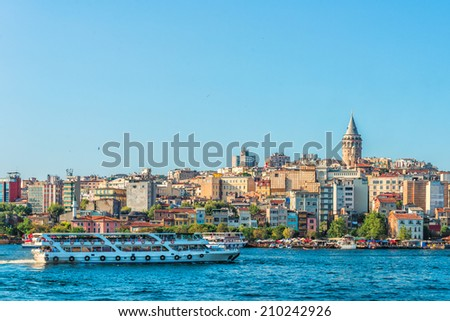 A ferry passes along the Bosphorus with Galata Tower in the distance. - stock photo