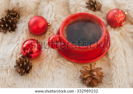 A festive and cozy composition with a red cup of hot coffee, fir twigs, cones, cinnamon sticks and Christmas tree decorations on a white fur surface