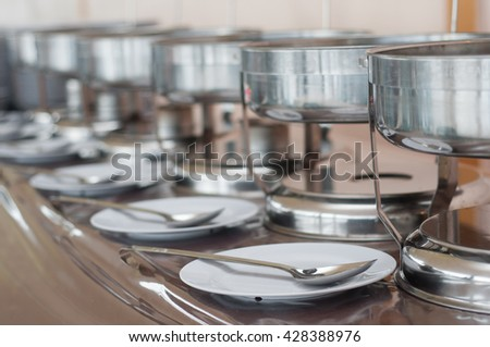 A few chafing and dinner plate on a banquet table with a blurred background of a wedding decorations. selective focus