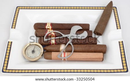 A few cigars, cutters, and hygrometer are in an ashtray - stock photo