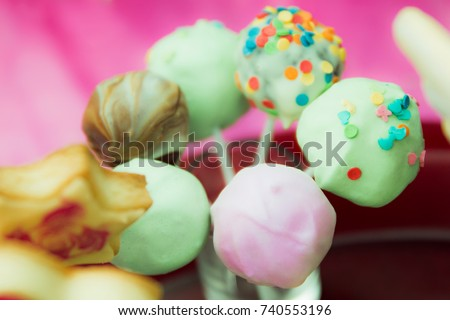 A few colorful candies in the shape of a ball on a stick, covered with icing and confetti. Soft focus.