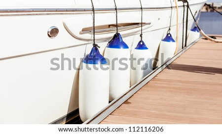 A few fenders suspended between a boat and dockside for protection/ Maritime fenders - stock photo