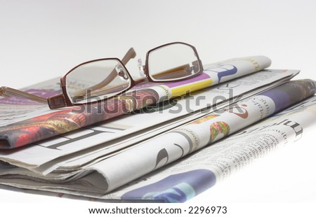 a few fresh newspaper with the pair of glasses on the table
