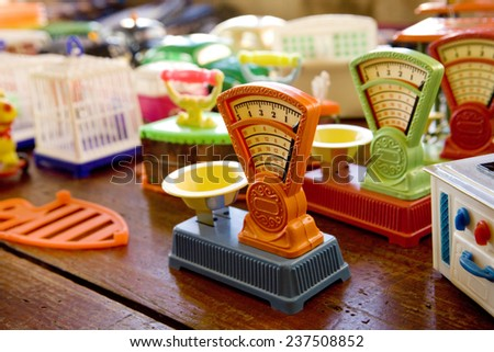 A few multi colored plastic weight scales in a toy store.  Toy Weight Scale. - stock photo