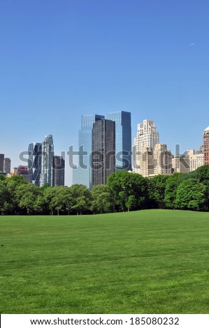 A field of green grass, a line of trees, and some tall buildings. - stock photo