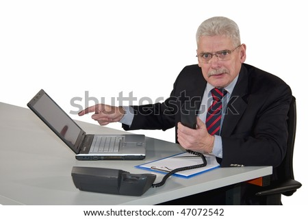 a fierce looking caucasian senior manager being in a discussion on the phone and pointing at his laptop, isolated on white background