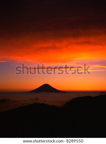 A fiery sunrise over the silhouette of sacred Fuji - stock photo