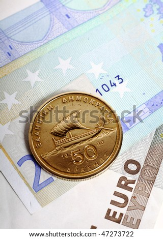 A fifty drachma coin lying on euro notes which replaced the Greek currency. Greece's economic woes are now seen as a threat to the stability of the euro. - stock photo