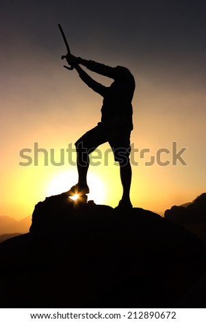 A figure holding a sword above his head in silhouette against a desert sunrise
