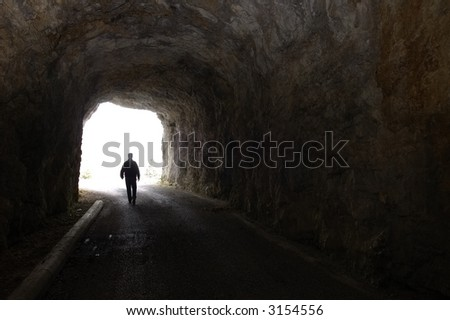 A figure walking out of a dark tunnel into bright daylight - stock photo